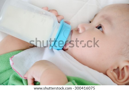 Pretty baby boy drinking milk from bottle - stock photo
