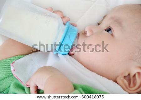 Pretty baby boy drinking milk from bottle - stock photo