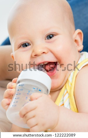 Pretty baby boy drinking water from bottle - stock photo