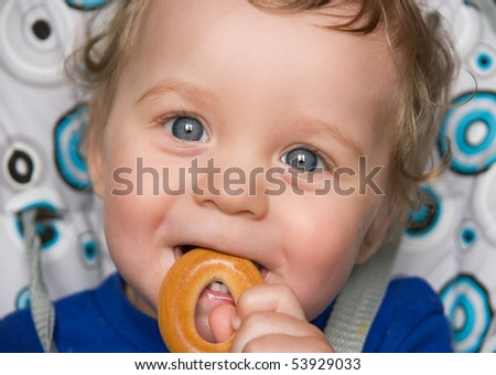 pretty baby boy laughing portrait with bread ring - stock photo