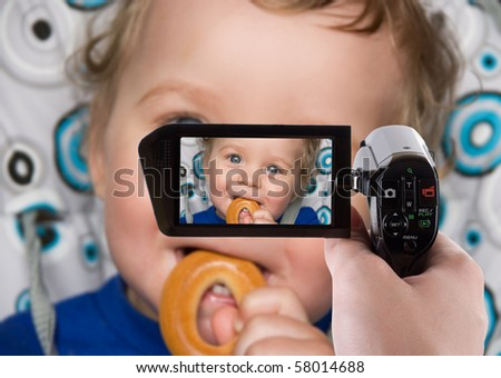 pretty baby boy laughing portrait with bread ring recording at camcorder - stock photo