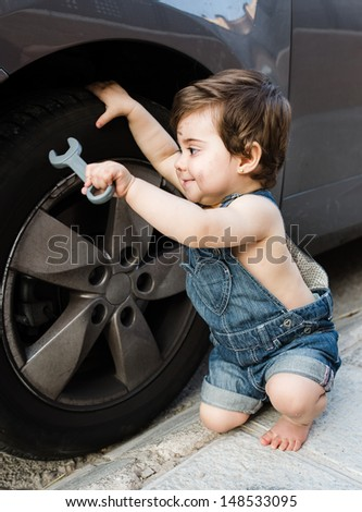 Pretty baby dressed as mechanic smiling and repairing a real car - stock photo