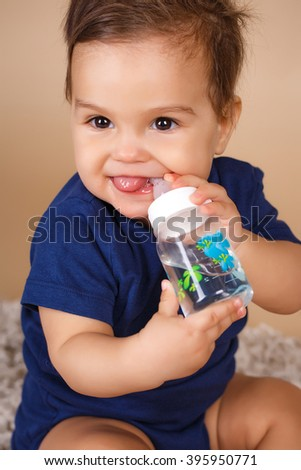 Pretty baby drinks water from bottle lying on bed. Child weared diaper in nursery room. baby holding bottle and drinking water. sweet funny baby drinking water - stock photo