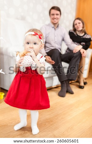 Pretty baby girl of foreground with parents on background - stock photo