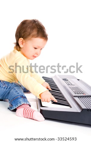 Pretty baby girl playing electric  piano, isolated