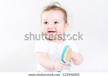 Pretty baby girl playing with a hair brush - stock photo