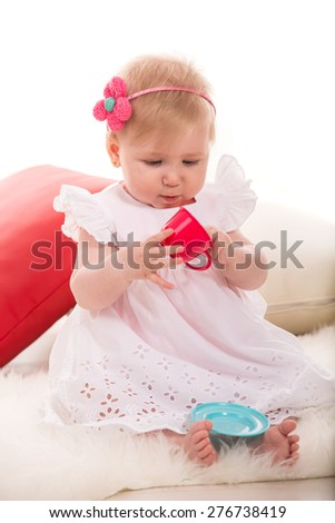Pretty baby girl playing with cup toy and sitting on fluffy blanket