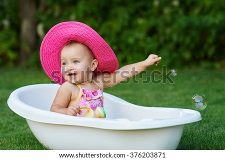 Pretty baby girl playing with water in little plastic bath outdoors in the garden. - stock photo