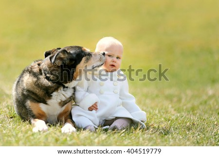 Pretty Baby Girl Sitting Outside with her Pet German Shepherd Dog as he Kisses Her Cheek - stock photo