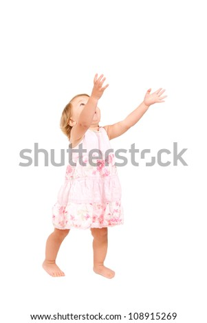 pretty baby girl standing and holding hands in the air, reaching for something, catching something. Ready for your text or logo. Isolated on white background with clipping path