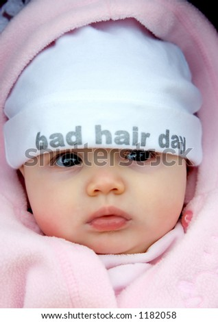 Pretty baby girl with funky hat on that says bad hair day
