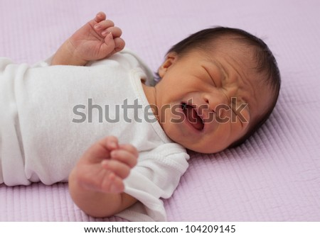 Pretty Baby Newborn Asian infant girl upset and crying with wrinkles in face - stock photo