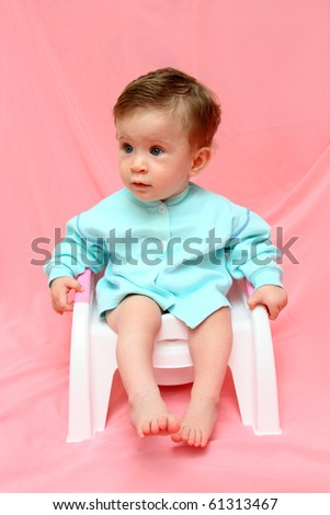 pretty baby sitting on chamber-pot - stock photo