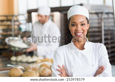 Pretty baker smiling at camera in the kitchen of the bakery - stock photo