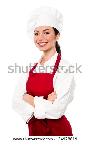 Pretty baker woman posing with confidence, arms folded. - stock photo