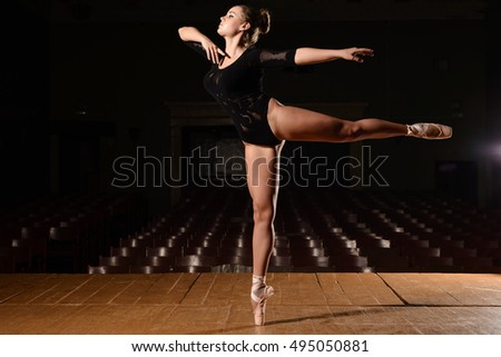 Pretty ballerina in pointe shoes is standing making flap leg on the stage