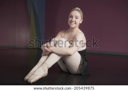 Pretty ballerina sitting and smiling at camera in the ballet studio - stock photo