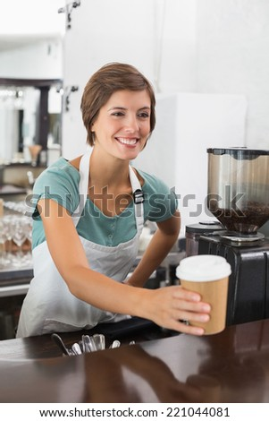 Pretty barista holding disposable cup at the coffee shop - stock photo