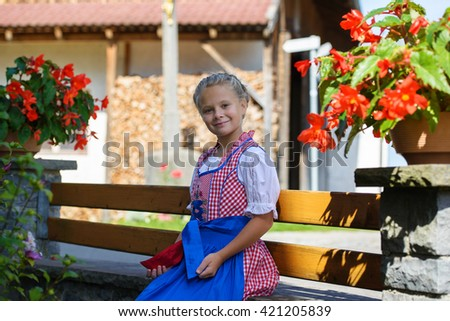 Pretty bavarian girl with flowers on the farm in Germany . - stock photo