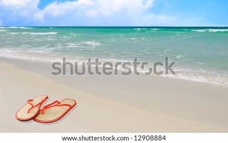 Pretty beach and ocean filled with straw sandals on sand - stock photo