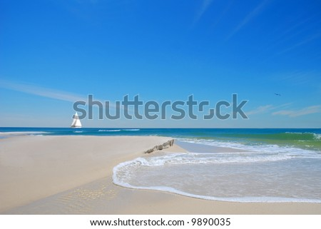 Pretty beach sand and dune with gentle waves with sailboat in distance under blue sky - stock photo