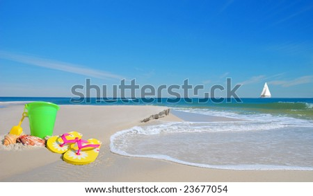 Pretty beach sand toys on dune with gentle waves with sailboat in distance under blue sky - stock photo