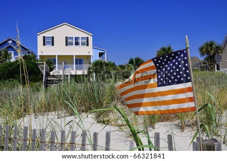 Pretty beach scene with rental home, dune and American flag. - stock photo