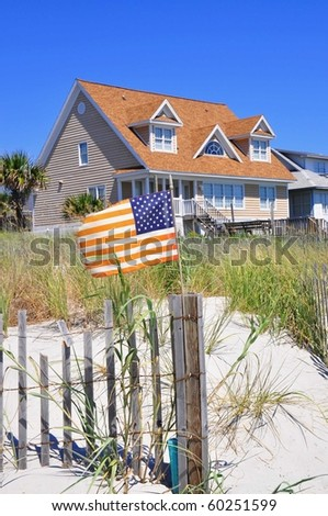 Pretty beach scene with rental home, dune and American flag. Perfect for cover art. - stock photo