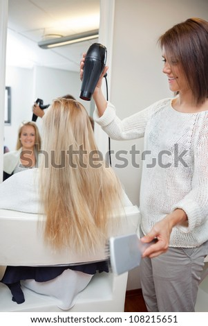 Pretty beautician blow drying female's long blond hair at parlor