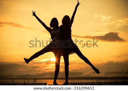 Pretty beautiful brunette and blonde girl friends having fun. Both standing in park and smiling (laughing). Concept of female friendship.