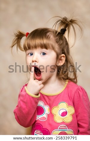 Pretty beautiful cute surprised girl  kid with two tails. Baby girl , looking at camera - stock photo