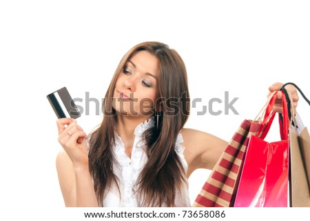 Pretty beautiful girl holding gift credit card in one hand and shopping bags presents in another on a white background. - stock photo
