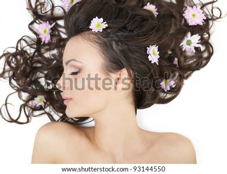 Pretty beautiful girl lying with bright flowers in her hair bright makeup isolated on white - stock photo