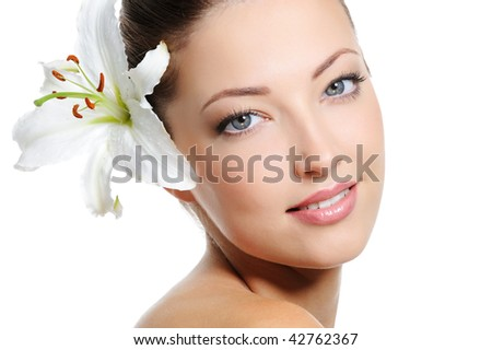 Pretty beautiful woman face with health skin and white lily in her hairs - stock photo