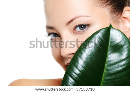 Pretty beautiful woman's face behind the large green leaf - stock photo