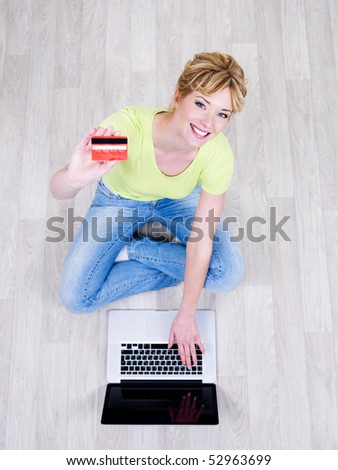 Pretty beautiful young woman sitting on the floor with credit card and using laptop - stock photo