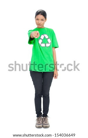 Pretty black haired model wearing recycling tshirt pointing at camera on white background - stock photo