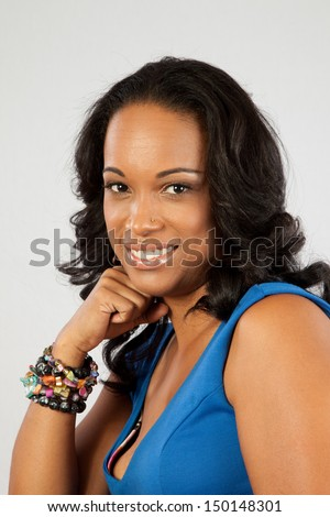 Pretty black woman in a blue blouse, smiling warmly at the camera