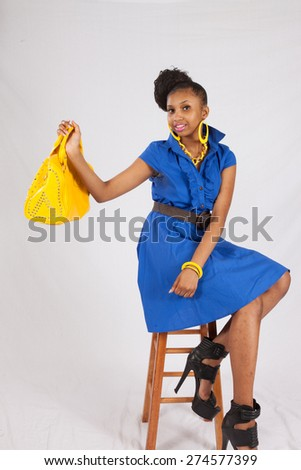 Pretty black woman in a blue dress and yellow purse, looking at the camera with a happy smile - stock photo