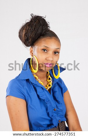 Pretty black woman in a blue dress  , looking at the camera thoughtfully  - stock photo