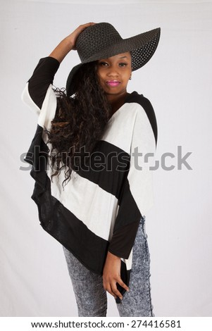 Pretty black woman in a hat and black and white blouse,looking thoughtfully at the camera - stock photo