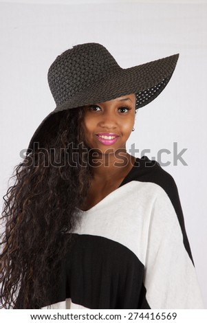 Pretty black woman in a hat and black and white blouse, smiling at the camera - stock photo
