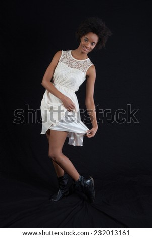 Pretty black woman in a white dress, standing and looking at the camera and dancing - stock photo