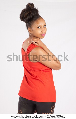 Pretty black woman in blouse looking thoughtfully over her shoulder