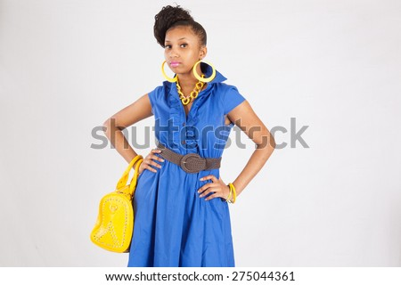 pretty black woman in blue dress looking thoughtful with a yellow purse - stock photo