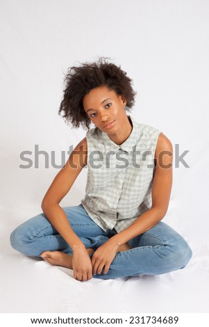 Pretty black woman in blue jeans, sitting and  looking at the camera with a playful smile of pleasure