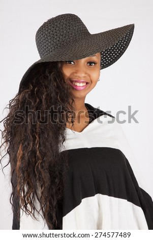 Pretty black woman in hat and black and white blouse, looking at the camera with a happy smile - stock photo