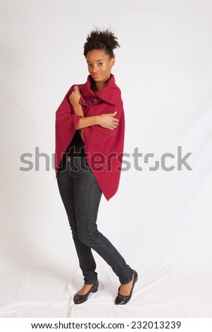 Pretty black woman in red cape, standing and looking at the camera with a pleased smile - stock photo