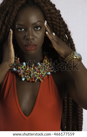 Pretty black woman in red outfit and long dreadlocks, looking thoughtful with her hand on her head as if she had a headache