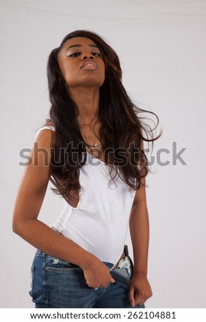 Pretty Black woman in white blouse and blue jeans looking at the camera thoughtfully - stock photo
